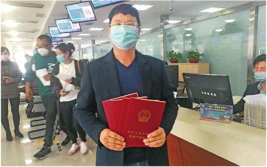 3月25日,寿光市政务服务中心大厅,李凯展示领取的四个仓库的不动产权证书。□记者 杨国胜 石如宽 报道