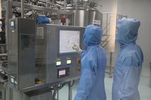 工作人员正在生产车间监看设备运行情况。