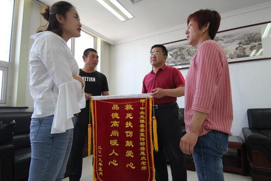 老人的家属为蒋惠庆(右二)赠送锦旗