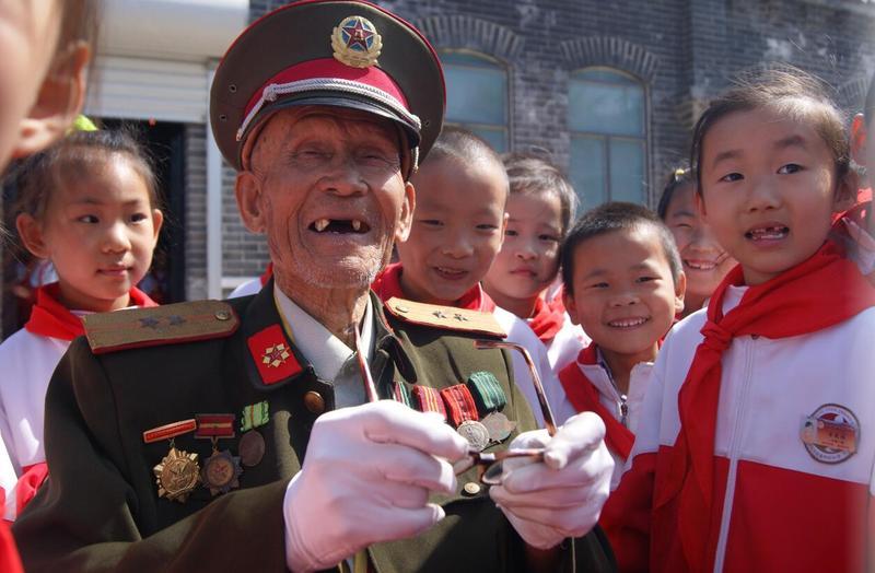 东营市少先队员到牛庄烈士祠开展红领巾寻访活动,抗战英雄为少先队员讲述革命故事