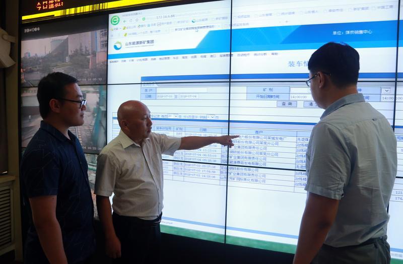 王树红(中)和同事分析煤销情况