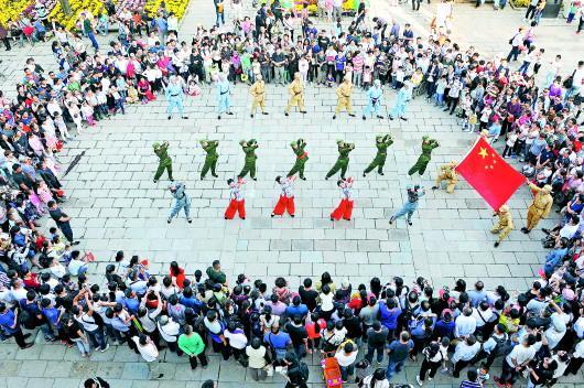 10月6日,枣庄台儿庄古城为庆祝新中国成立70周年举行文艺演出,游客纷纷驻足观赏,击掌点赞。(□记者 张环泽 报道)