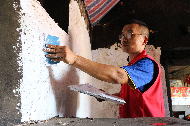 ▲志愿者在孤寡老人生宝亮家整修老房。记者 董梅雪 报道