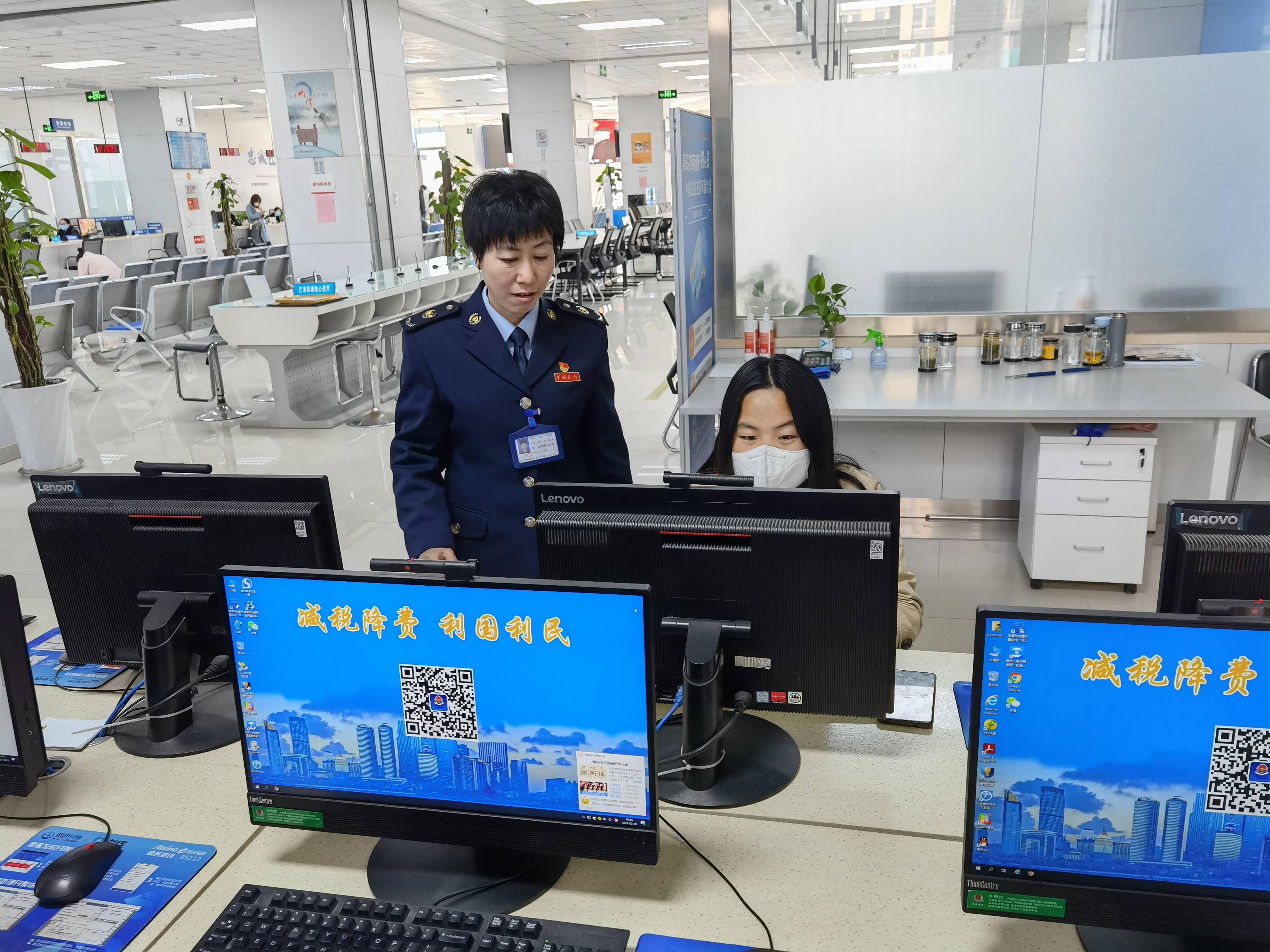 李静(左)正在指导纳税人办理税务业务。
