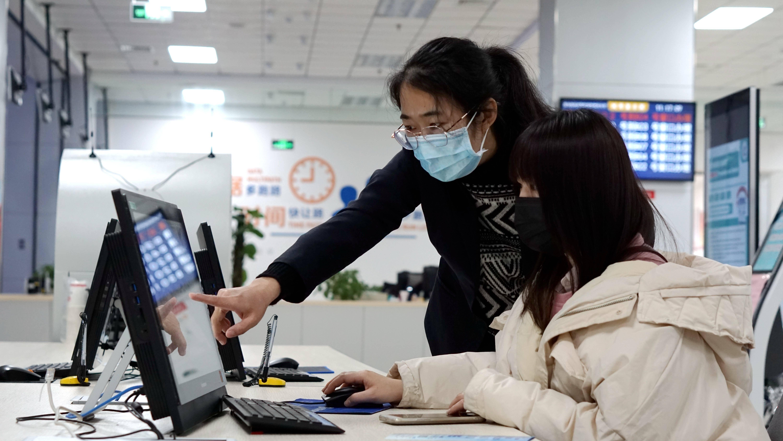 在青岛西海岸新区政务服务大厅二楼自助服务区,市民蔡女士在大厅工作人员的指导下,很快就完成了企业登记业务。(胡全福 摄)