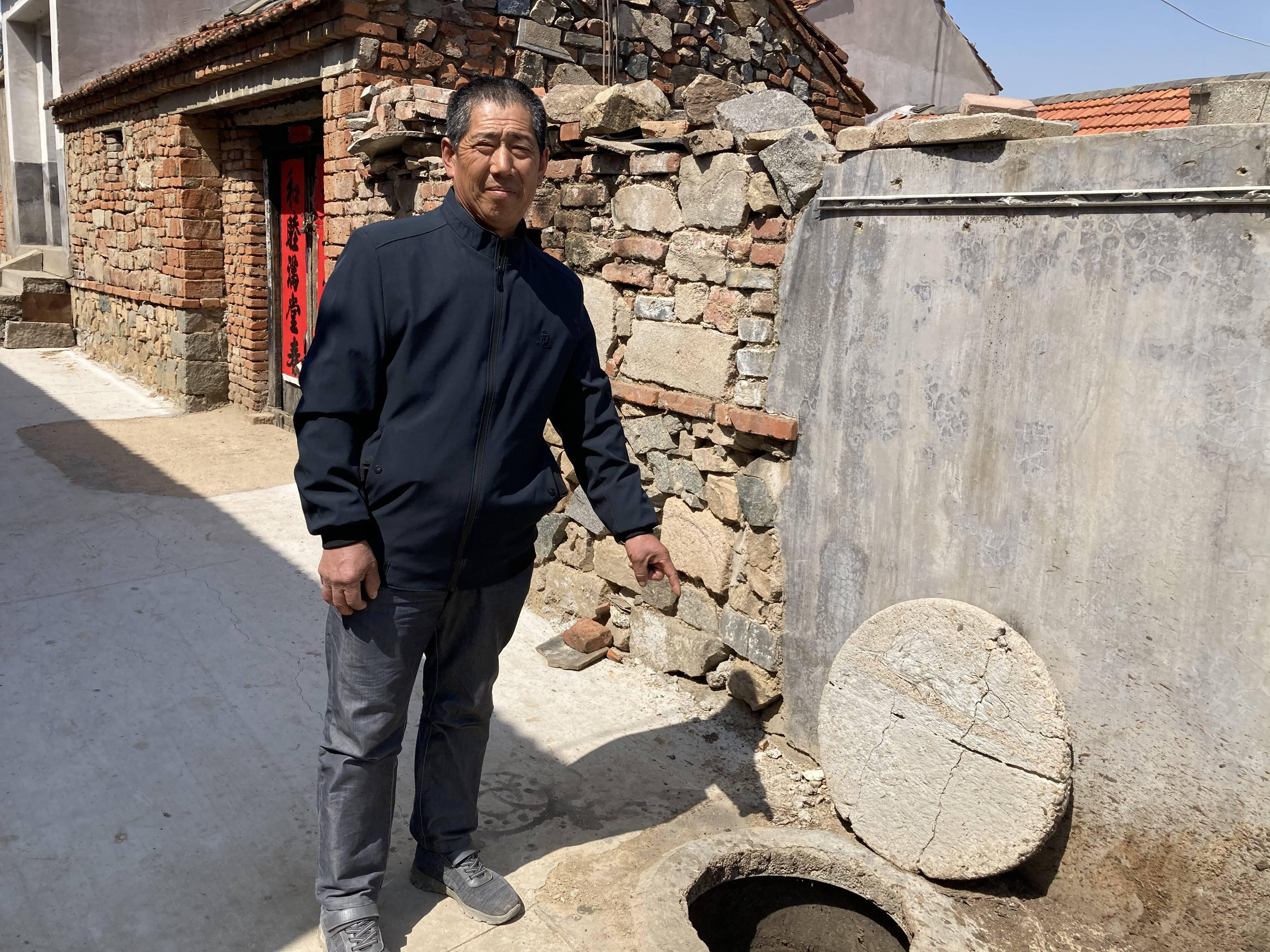 刘法强向记者介绍当时浸湿毯子的猪尿池。