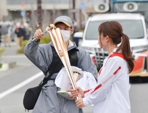 工作人员为火炬手重新点燃圣火,图源:日本《每日新闻》