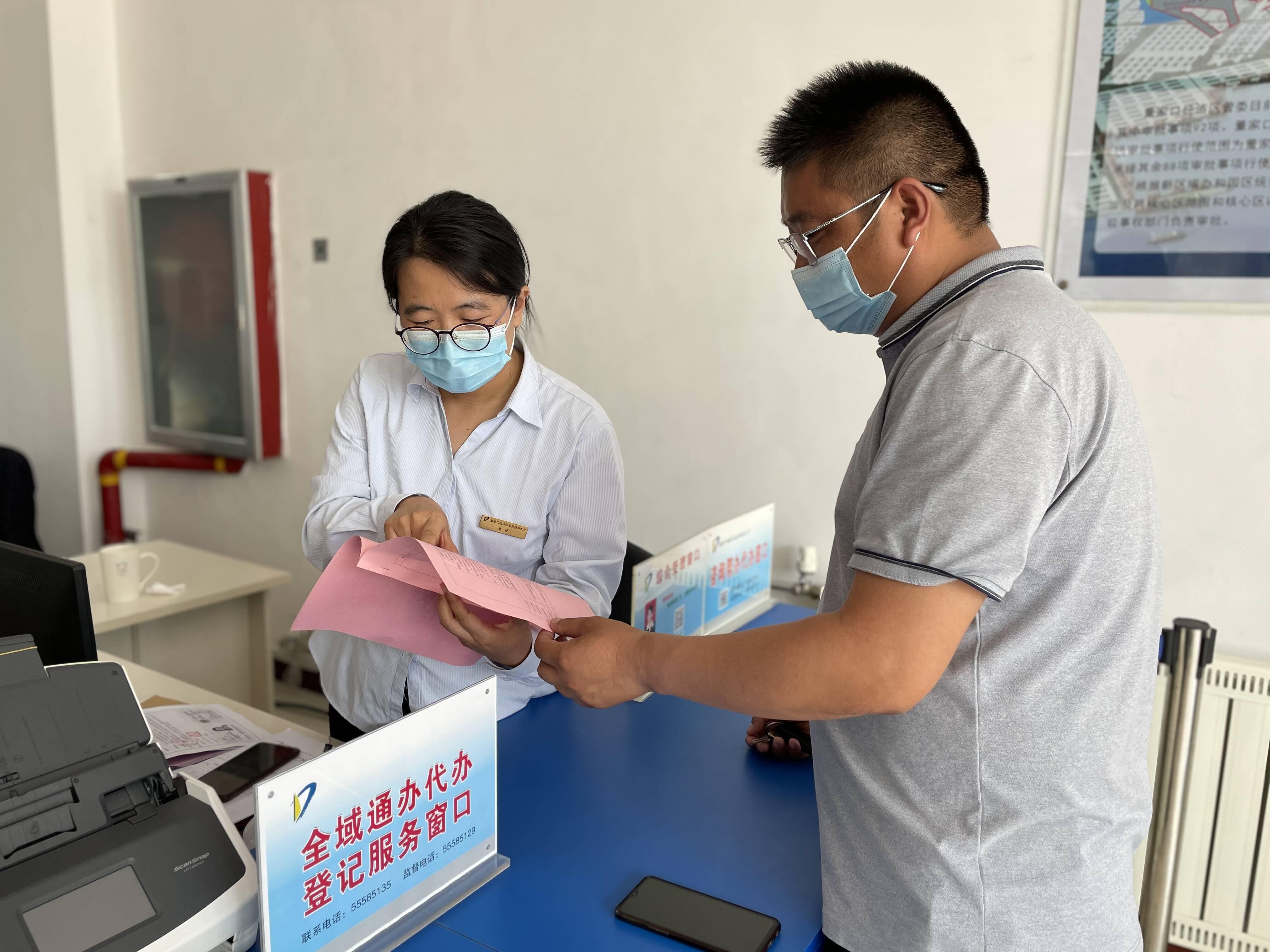 政务服务大厅工作人员耐心向企业负责人讲解审批流程。