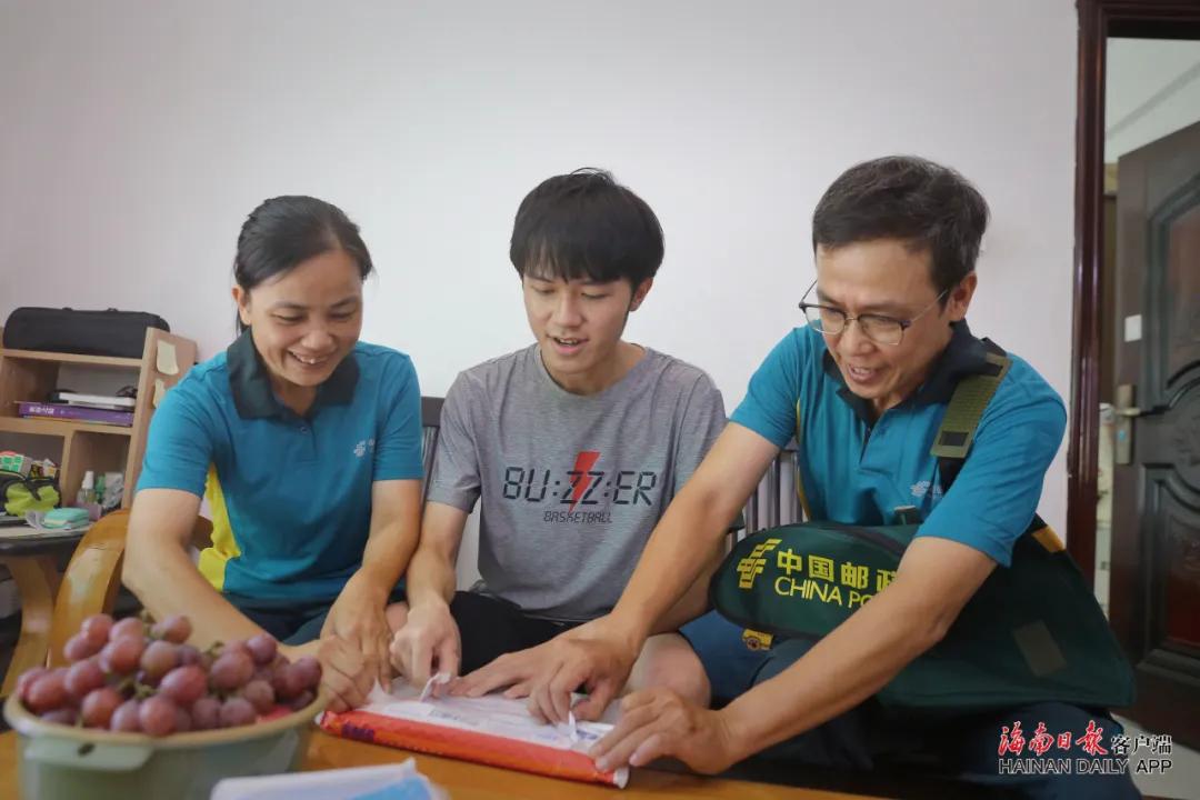 父亲卢志强(右)、儿子卢海山(中)、母亲王金连(左)一家三口一起拆开北京大学录取通知书。海南日报记者 张茂 摄