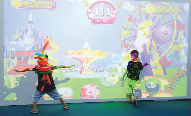 孩子们在大屏体感游戏前玩耍。记者 王培珂 摄