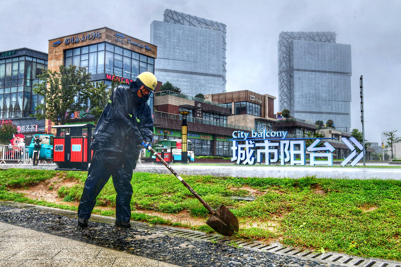 防汛工作人员护理排水设施。记者 李亮 摄