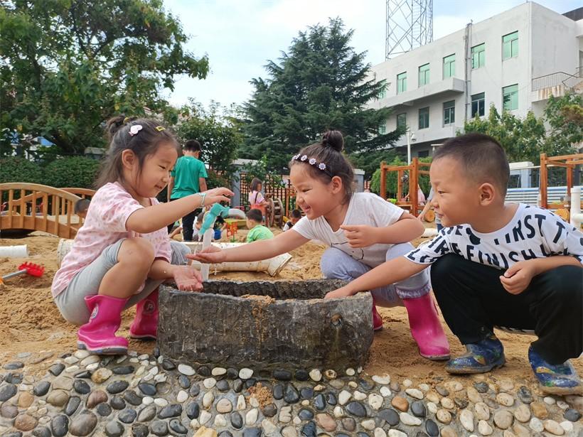 孩子们在灵珠山中心幼儿园沙水区戏水。