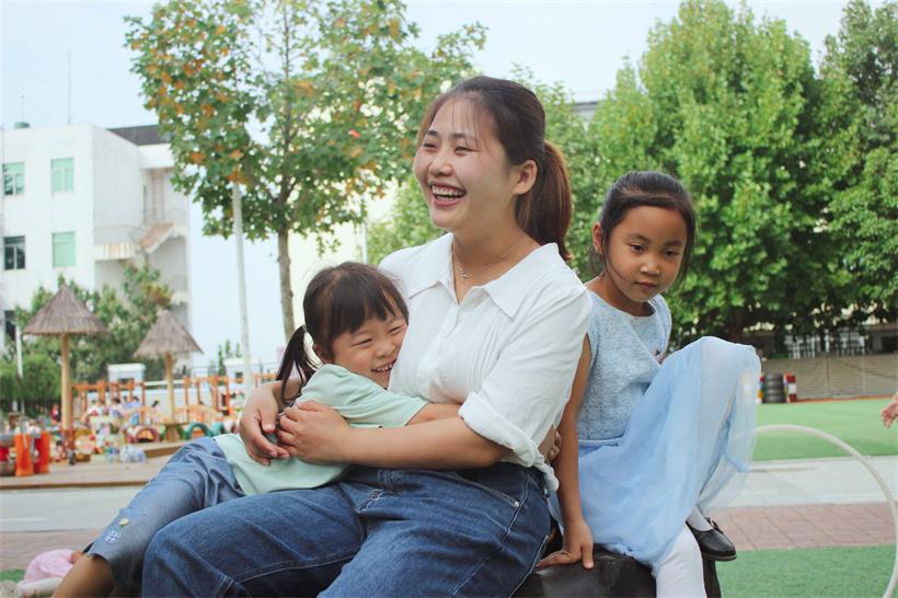 灵珠山中心幼儿园的老师与孩子们一起玩耍。