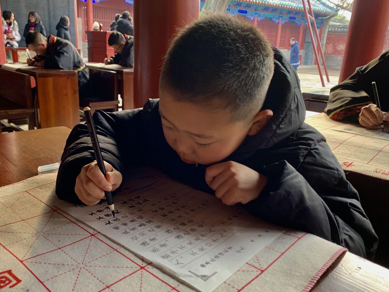 小游客认真抄写儒学经典。 刘鸿儒 报道