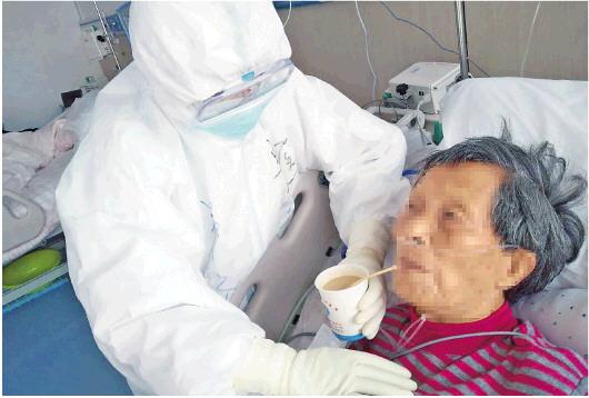 □王淑娴 王凯 报道 2月22日,大别山区域医疗中心南楼7层感染隔离病房,山东医疗队队员、单县中心医院护士郑扬在给患者喂食流汁。