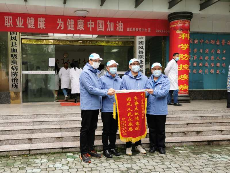 韩超(左一)与同在黄冈市团风县的队员们收到当地工作人员赠送的锦旗。