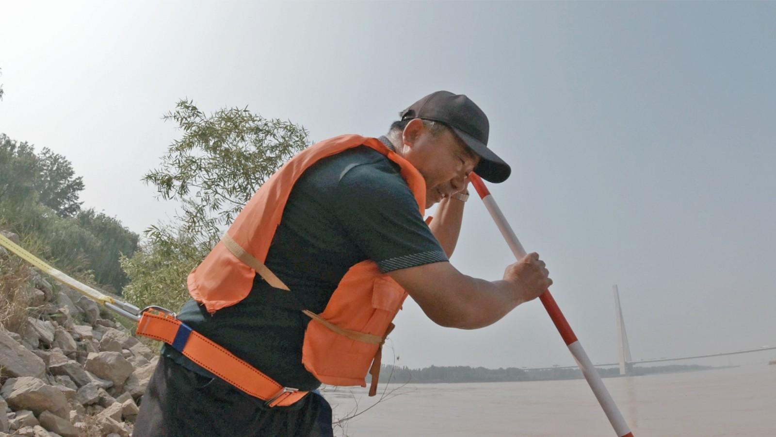 孙宝良用探摸杆检查黄河岸边的护堤根石是否走失。记者 赵国陆 摄