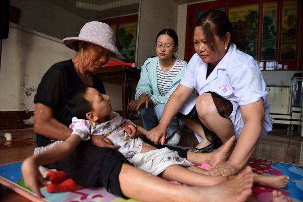 2020年6月30日,在郯城县红花镇老周圩子村,王玉红(右二)请来医生为先天脑瘫患儿小凯乐看病。