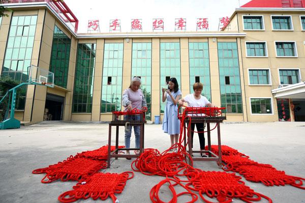 2020年6月24日,在郯城县红花镇一家中国结加工企业,王玉红拍摄用于网络推销的编织程序。