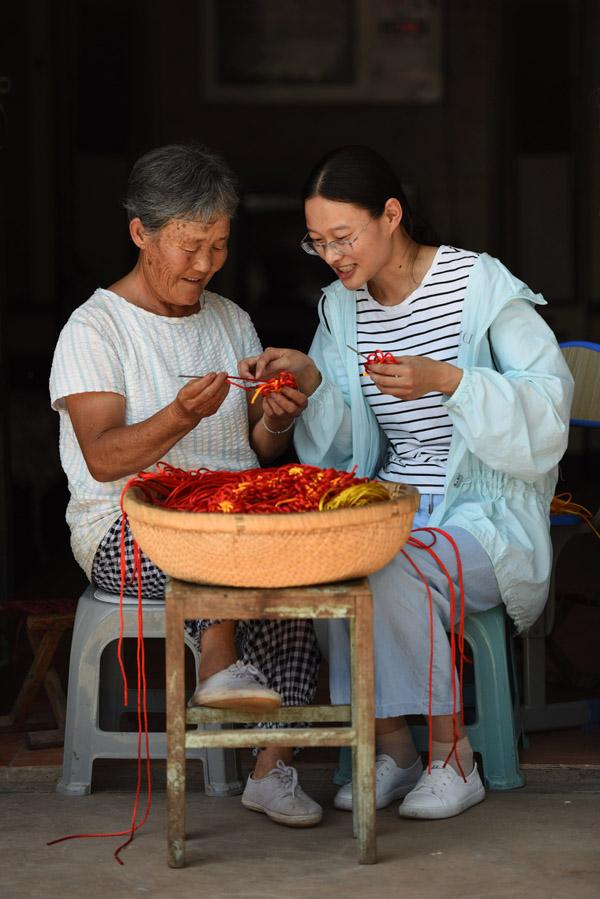 2020年6月30日,在郯城县红花镇老周圩子村,王玉红(右)向贫困户庄华云老人传授中国结的编织方法。