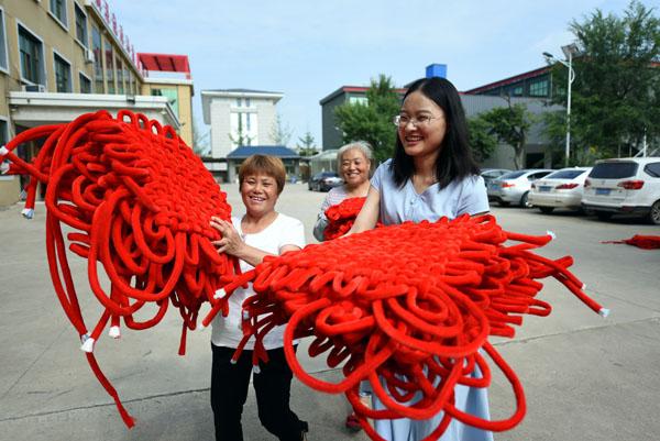 2020年6月24日,在郯城县红花镇一家中国结加工企业,王玉红(右一)帮助工人搬运中国结。
