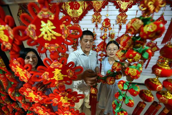 2020年6月24日,在郯城县红花镇一家中国结加工企业,王玉红(右一)向企业负责人了解中国结的品种和销路情况。