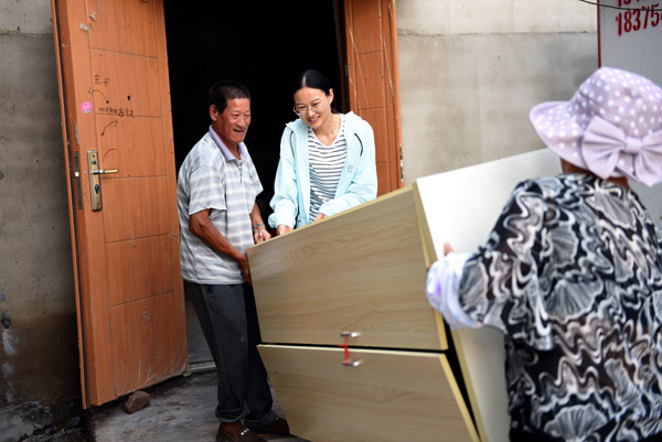 2020年6月30日,王玉红(右)为郯城县红花镇老周圩子村贫困户肖尢山(左一)送来了衣橱。