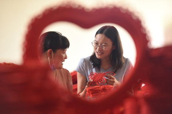 2020年6月24日,在郯城县红花镇一家中国结加工企业车间,王玉红(右)向工人师傅学习编织技艺。