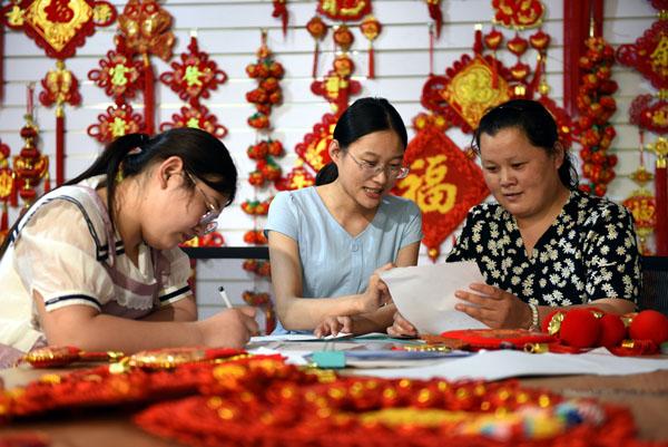 2020年6月24日,在郯城县红花镇一家中国结加工企业,王玉红(中)帮助企业设计新产品。