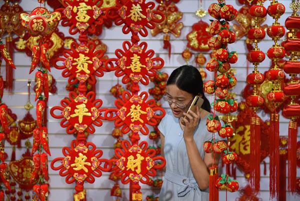 2020年6月24日,在郯城县红花镇一家中国结加工企业,王玉红帮助企业联系客户。