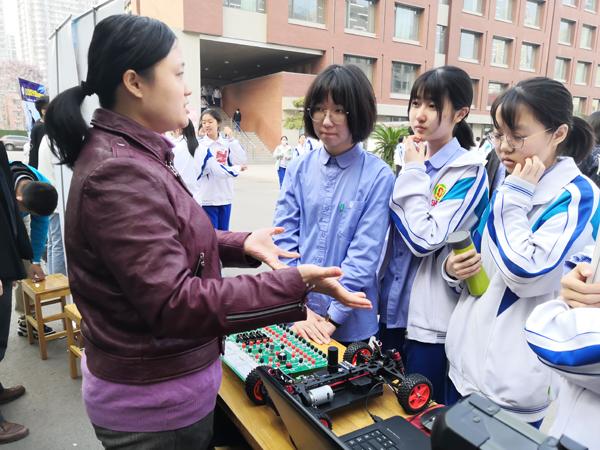"""此次科技节校方邀请了高校科技社团入校宣讲,和同学们分享最前沿的科研动态。图为山东大学微电子学院的老师在为同学们讲解参展的""""北斗人工智能""""项目成果。"""