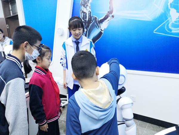 """科技节的""""小小科学家"""",小朋友们与智能机器人的互动。不少中小学生也参加了此次科技节,据校团委书记任兴华介绍,此次活动的最大亮点是初中、高中、大学的对接。"""