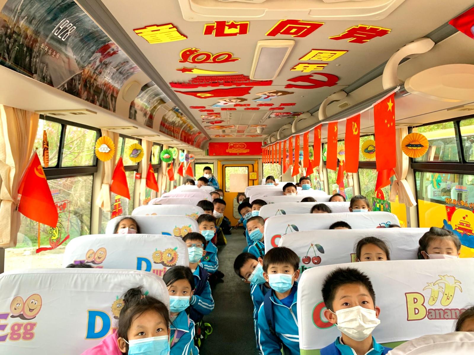 三里河小学同学们在观看车载电视上的红色故事