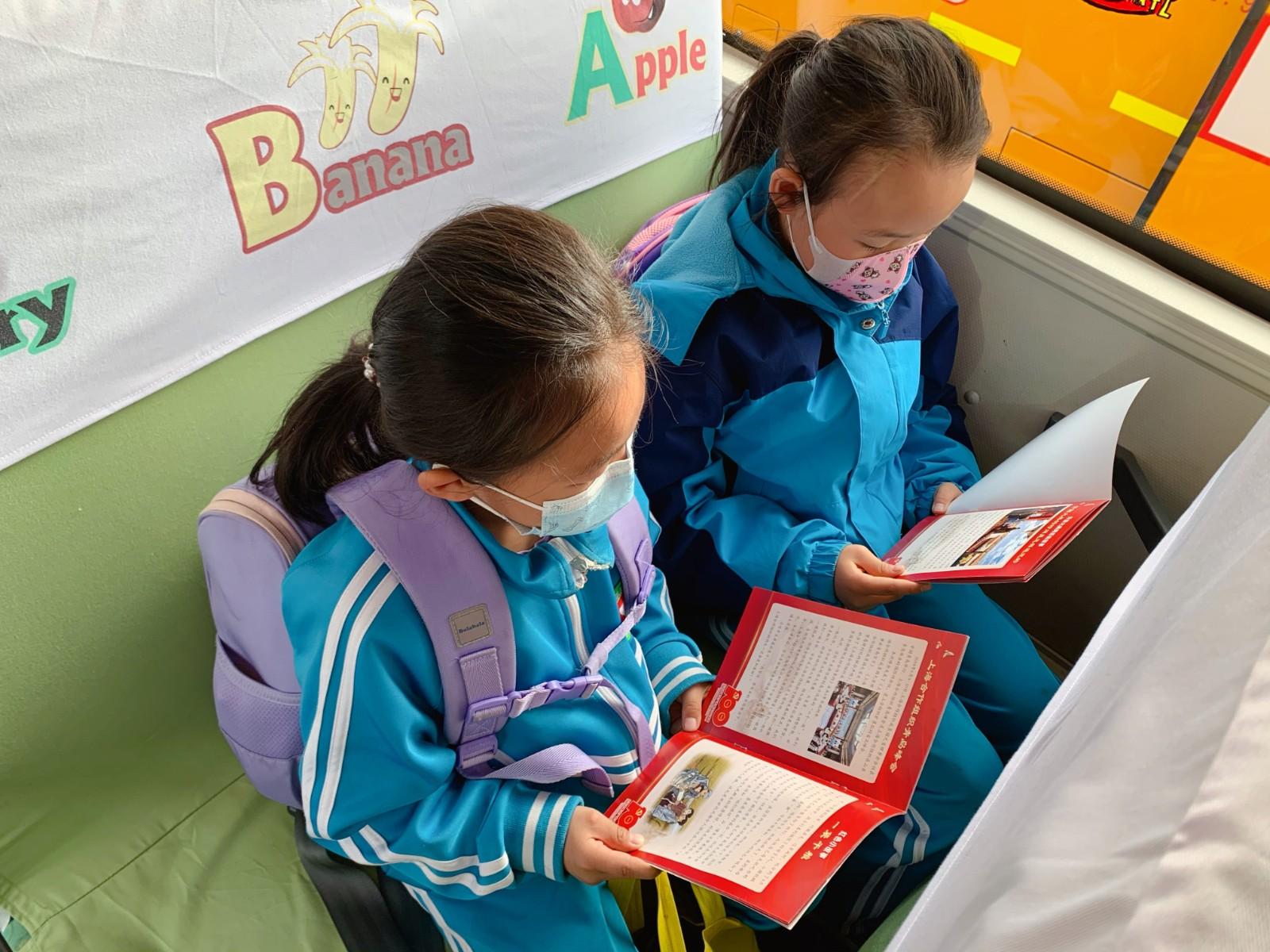 三里河小学学生利用坐班车的时间看红色小故事