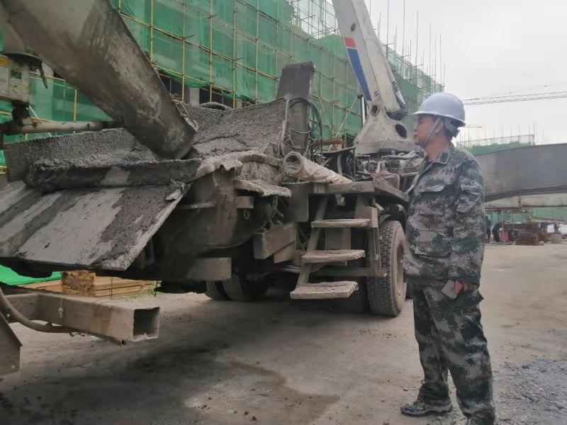 图为工作队队员现场督导混凝土浇筑