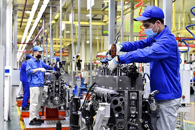 4月22日,在位于山东潍坊的潍柴集团总装车间,工人在流水线上装配发动机。