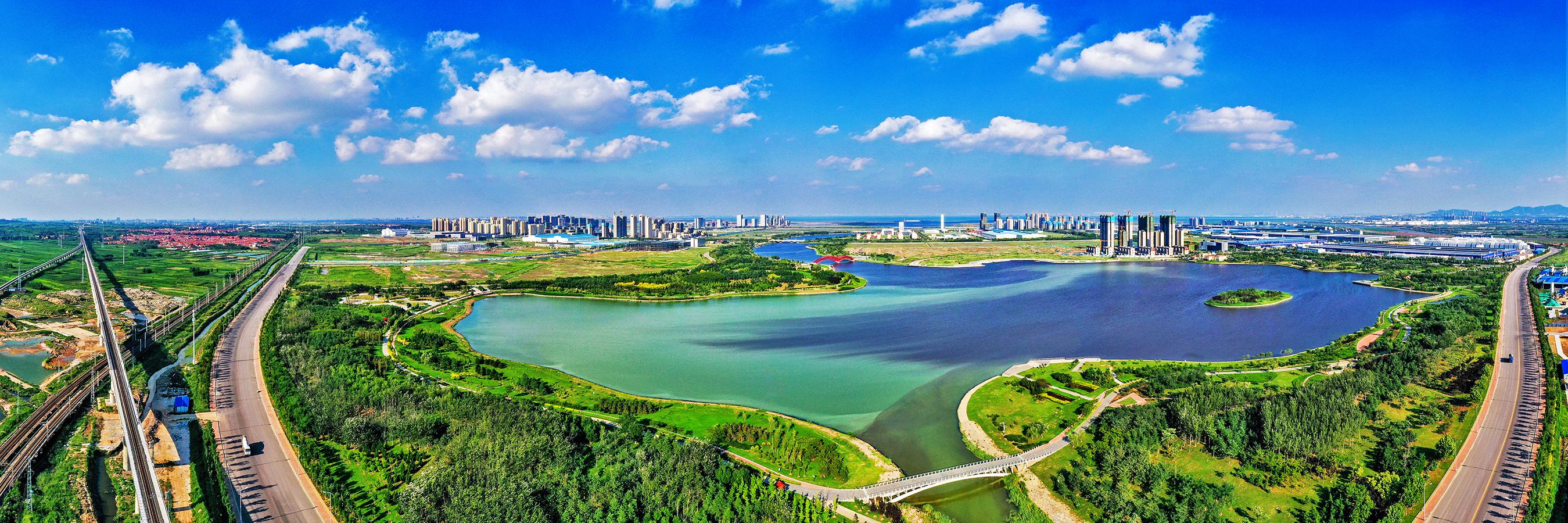 """上合示范区聚焦""""4+1""""中心建设任务,积极拓展国际物流、现代贸易、双向投资、商旅文化和海洋等领域合作。图为上合示范区鸟瞰图。"""
