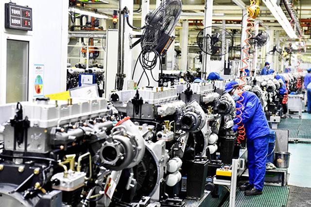 潍柴集团总装车间,工人在流水线上装配发动机。