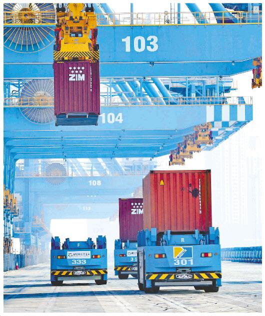 4月7日,位于山东自贸区青岛片区的山东港口青岛港全自动化码头,自动导引车快速行进装运货物。(□记者 卢鹏 通讯员 张进刚 报道)